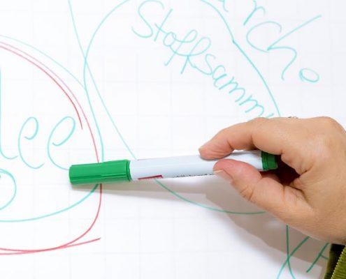Hand zeigt mit einem Stift auf eine Ideen-Skizze