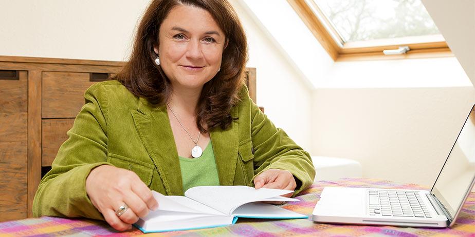 Ulla Ruths an einem Tisch sitzend und in einem Buch blätternd